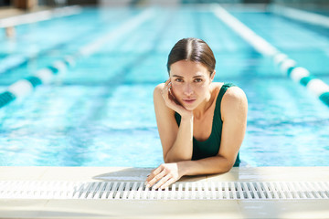 Relaxed wet woman in swimwear leaning over edge of swimming-pool at spa resort