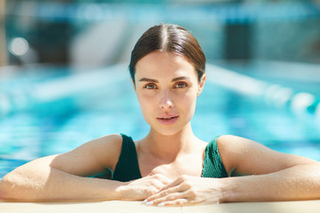 Young restful woman sitting in swimming-pool while spending vacation at spa resort
