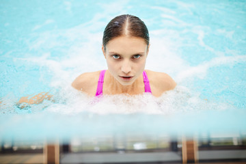 Fit girl enjoying stream of water during spa procedure in swimming pool