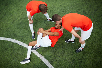 Two young football players in uniform leaning over their mate lying on field with hurt knee
