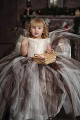 little blond girl in lush dress with wicker basket in hands