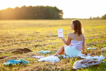 Dressy woman sitting in the middle of the field between scattered cloth and holding a tablet with SALE title during sunset. Fast fashion over-production and pollution concept.