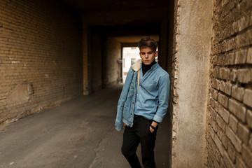 Stylish handsome man in a denim shirt with a trendy denim jacket posing outside near a brick wall