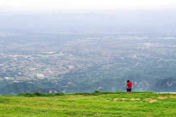 Photographer stand on the cliff and taking landscape photo at Phu Tub Berk Mountain, Thailand