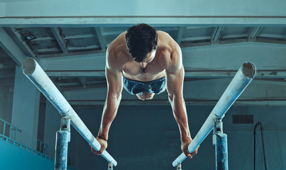 The sportsman performing difficult gymnastic exercise at gym. The sport, exercise, gymnast, health, training, athlete concept. Caucasian fit model Wall mural
