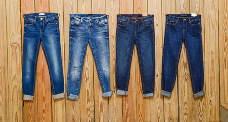 Four blue Jeans- wooden background
