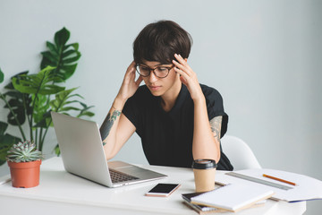 Tired businesswoman in glasses at workplace in office.