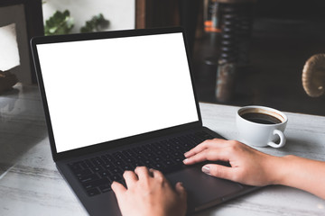 Mockup image of a woman using and typing on laptop with blank white screen and coffee cup on table in modern cafe