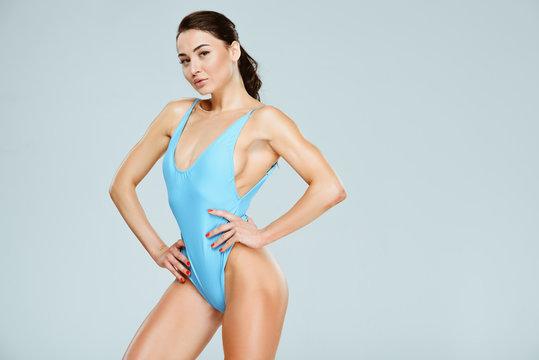 sexy sportive woman posing in blue swimwear isolated on grey