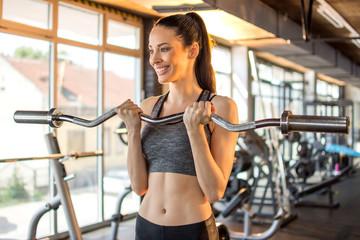 Fit slim woman lifting curl bar barbell in modern gym.