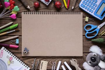 Top view of blank notebook cover and stationery accessories on wood background with copy space. Back to school background concept flat lay with copy space.