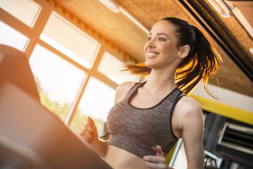 Attractive sportswoman on running track treadmill machine in gym.