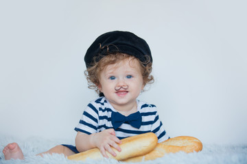 Little baby with mustache, beret and baguette on white background.