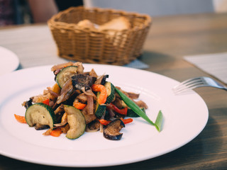 Pork roast with vegetables on white plate in table