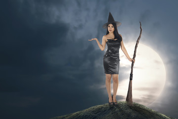 Young asian witch woman with hat and broomstick