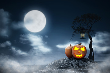 Jack-o-lantern above the rock with lantern hanging on the branch