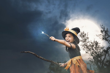 Cute asian little witch girl with magic wand on her hands