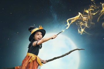 Beautiful asian witch girl using the magic wand