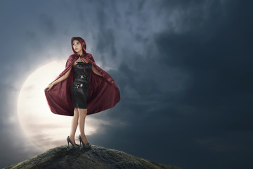 Pretty asian witch woman with red hooded cloak