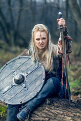 Blonde young beautiful viking warrior woman in forest with shield and sword in hand. Northern woman resting on a log after battle.