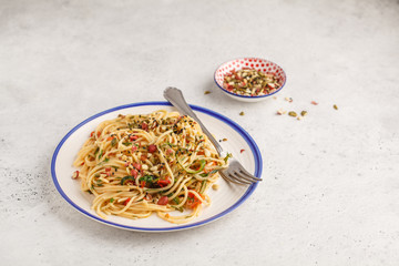 Healthy vegan pasta with zucchini, tomatoes and nuts.