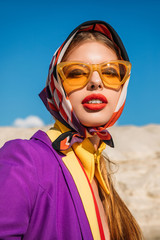 portrait of elegant young woman in trendy yellow sunglasses