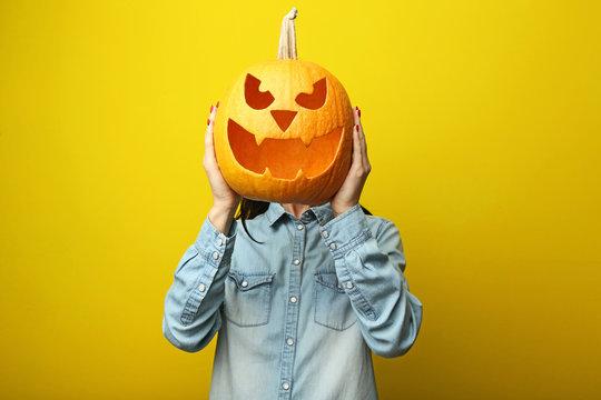 Female hands holding halloween pumpkin on yellow background