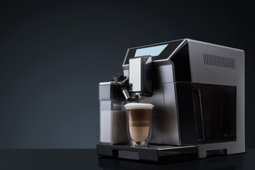 Coffee machine without flying coffee beans across it on dark background. Concept studio shooting. High speed freezing photo