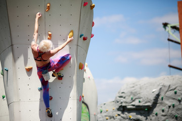 Photo from back of sports blonde with short haircut in sports clothes practicing on wall for climbing against blue sky