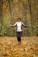 Image of sporty brunette jumping rope at autumn forest