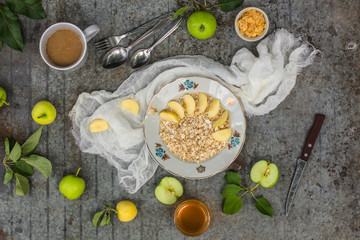 porridge - a portion a breakfast of oat flakes with honey, apples. food background
