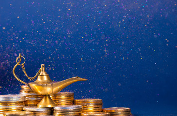 Magic lamp of wishes on stacks of gold coins with golden dust. Studio shooting.