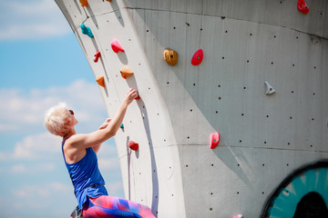 Photo of sportive woman on workout on climbing wall