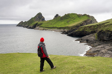 A visitor admiring the view of Dun island from the main St. Kilda island of Hirta