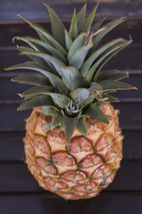 Vertical shot of whole ripe pineapple, a healthy tropical fruit favorite for its bromelain enzyme and antioxidant characteristics set on a wooden table with selective focus and purple, hazy filter