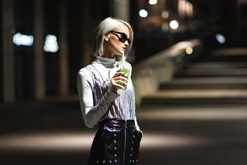 attractive young woman with mojito in plastic cup on dark street