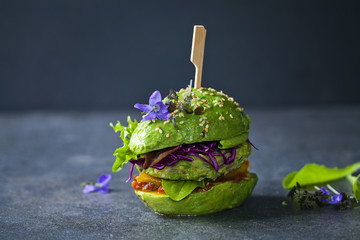 Fototapeta Avocado sandwich with green vegan burger,  roast yellow pepper and pickled red cabbage obraz