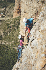 Young couple of climbers giving high five to celebrate a rockclimbing route in Los Mallos de Riglos, Spain