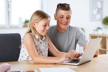 Cute girl using laptop with her brother