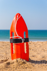 Orange buoy stands in beach sand