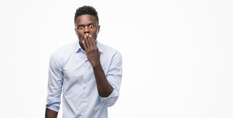Young african american man wearing a shirt cover mouth with hand shocked with shame for mistake, expression of fear, scared in silence, secret concept