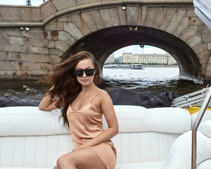 Portrait of a young brunette in sunglasses and a dress in a speedboat.