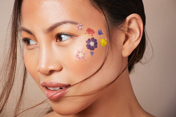 Woman with floral face paint on cheek