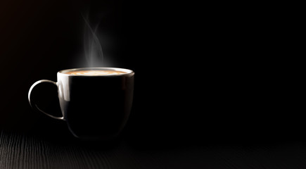Close up black hot coffee cup and smoke with latte art foam on black wood table at cafe.dark scene.banner space mock up for adding text.