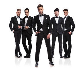 five elegant grooms in tuxedoes with relaxed leader in front