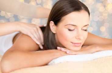 wellness, spa and beauty concept - close up of beautiful woman having massage over holidays lights...