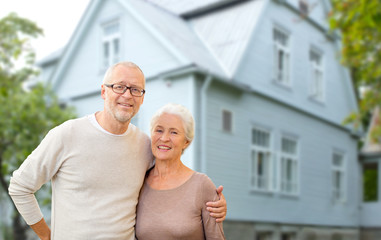 old age, accommodation and real estate concept - happy senior couple hugging over house background