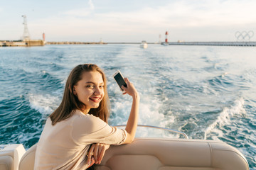 smiling long-haired girl floating on the Caribbean sea on a boat, taking pictures