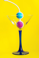 Color Kegel balls in a triangle cocktail glass. Concept of women health
