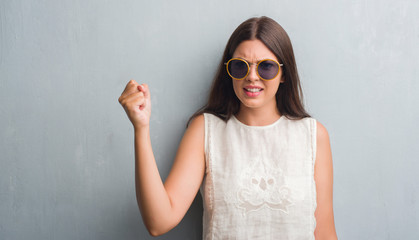Young brunette woman over grunge grey wall wearing retro sunglasses annoyed and frustrated shouting with anger, crazy and yelling with raised hand, anger concept